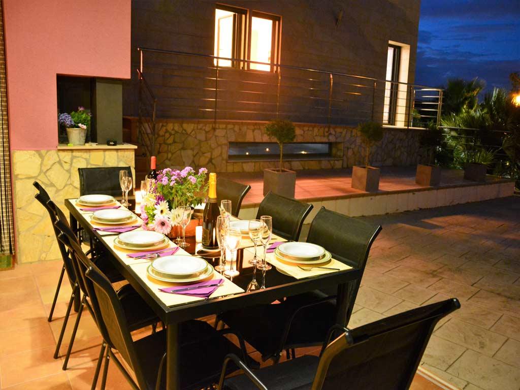 Villa Sitges de noche con comedor exterior.