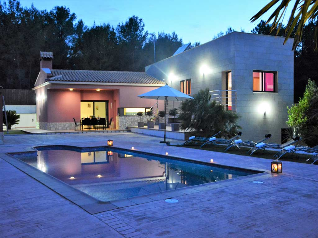 villa in Sitges at night with pool.