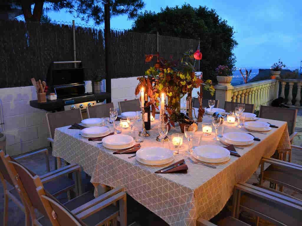 Villa en Sitges con iluminada mesa exterior de noche.
