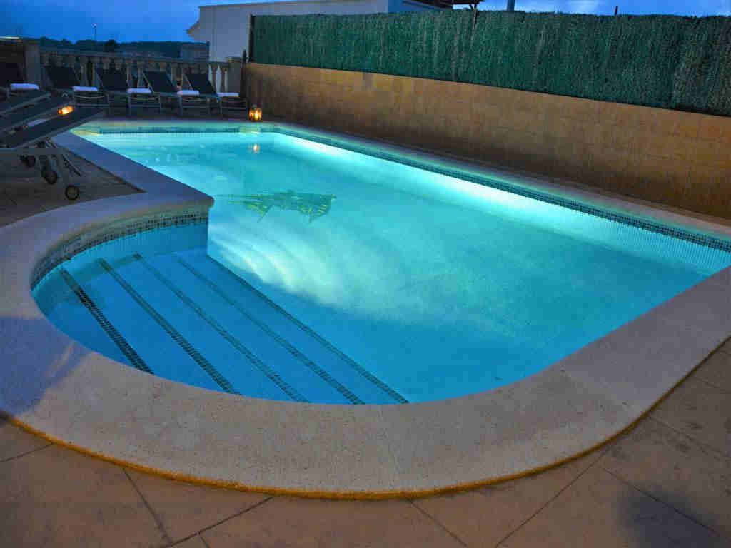 sitges villa with illuminated pool.